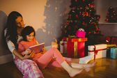 Mother and daughter using tablet beside the christmas tree — Stock Photo