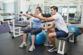 Personal trainer working with client on exercise ball — Stockfoto