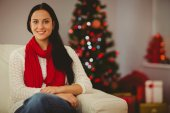 Pretty brunette relaxing on sofa at christmas — Stock Photo