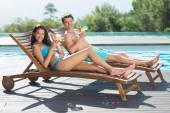 Couple sitting on sun loungers — Stock Photo