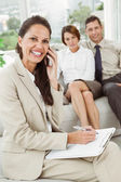 Businesswoman using mobile phone with colleagues behind — Stockfoto