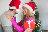 Smiling couple wearing santa hats — Stockfoto