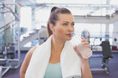 Fit brunette drinking water with towel around shoulders — Stock Photo