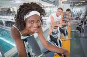 Three fit people working out on exercise bikes — Zdjęcie stockowe