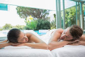 Couple lying on massage table at spa center — Stock Photo