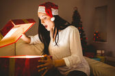 Festive brunette opening a glowing christmas gift — Stock Photo