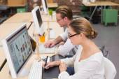 Concentrated casual photo editors using digitizer in office — Stock Photo