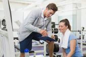 Personal trainer and client looking at clipboard together — Stock Photo