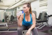 Fit brunette drinking from sports bottle — Stock Photo