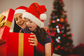 Festive mother and daughter opening a christmas gift — Stock Photo