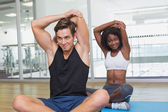 Fit couple warming up on exercise mats — Stock Photo