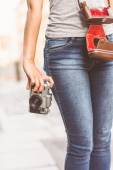 Close up of a girl wearing jean and holding a camera — Stock Photo