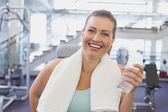 Fit brunette smiling with towel around shoulders — Stock Photo