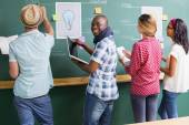 Creative business people at work by blackboard — Stock Photo