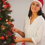 Woman hanging christmas decorations on tree — Stock Photo #56910015