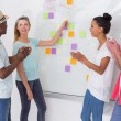 Creative team clapping hands by sticky notes on wall — Stock Photo #56910521