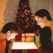 Festive mother and daughter opening a glowing christmas gift — Stock Photo #56911401