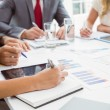 Mid section of executives writing notes in board room meeting — Stock Photo #56912381
