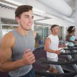 Fit man running on treadmill listening to music — Stock Photo #56912441
