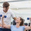 Personal trainer helping client lift dumbbell — Stock Photo #56912645