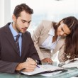 Businessman and secretary looking at diary in office — Stock Photo #56912901