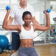 Personal trainer helping client lift dumbbells on exercise ball — Stock Photo #56913055