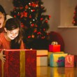 Festive mother and daughter opening a glowing christmas gift — Stock Photo #56913433