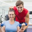 Personal trainer helping client lift dumbbells — Stock Photo #56913725