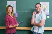 Creative business people with digital tablet by blackboard — Stock Photo