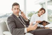 Businessman on call while secretary looks at diary — Photo