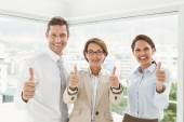 Confident happy business people gesturing thumbs up in office — Stock Photo