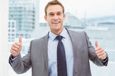 Smart businessman gesturing thumbs up in office — Stock Photo