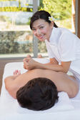 Female masseur massaging mans back — Stock Photo