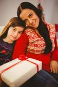 Festive mother and daughter holding christmas present — Stock Photo
