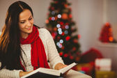 Pretty brunette reading on couch at christmas — Stock Photo