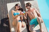 Couple with drinks on sun loungers by swimming pool — Stock Photo