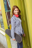 Redhead standing with his skateboard smiling at camera — Stock Photo