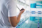 Swimming instructor holding stopwatch by the pool — Stockfoto