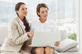 Young businesswomen using laptop — Stock Photo