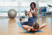 Personal trainer working with client on exercise mat — Stock Photo
