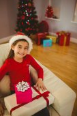 Festive little girl smiling at camera with gifts — Stock Photo