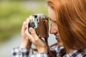Pretty redhead taking a picture with retro camera — Stock Photo
