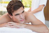 Young man lying on massage table at spa center — Stock Photo