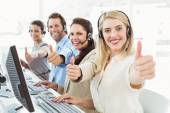 Colleagues with headsets using computers while gesturing thumbs up — Stock Photo