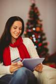 Pretty brunette shopping online with tablet at christmas — 图库照片