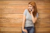 Cheerful redhead leaning against wall phoning — Stock Photo