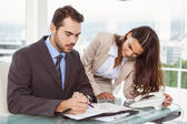 Businessman and secretary looking at diary in office — Stock Photo