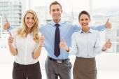 Business people gesturing thumbs up in office — Stock Photo