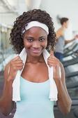 Pretty woman smiling at camera beside treadmills — Stock Photo