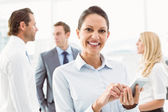 Businesswoman text messaging with colleagues in meeting behind — Stock Photo